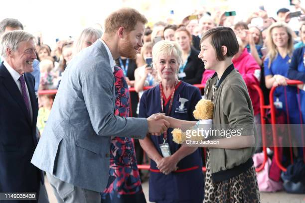 Prince Harry Duke of Sussex receives a gift from former patient Daisy Wingrove aged 13 as he arrives for a visit to the Oxford Children's Hospital on...