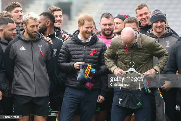 Prince Harry Duke of Sussex shares a joke with former Wales rugby captain Gareth Thomas and Chris Robshaw of Harlequins as he is presented with a...