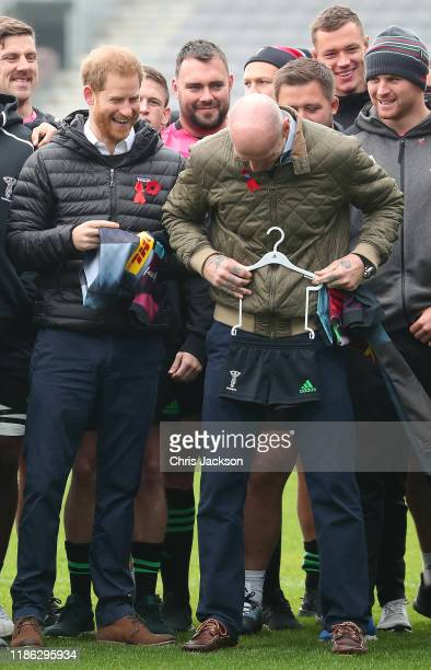 Prince Harry, Duke of Sussex shares a joke with former Wales rugby captain, Gareth Thomas as he is presented with a Harlequins kit for son Archie...