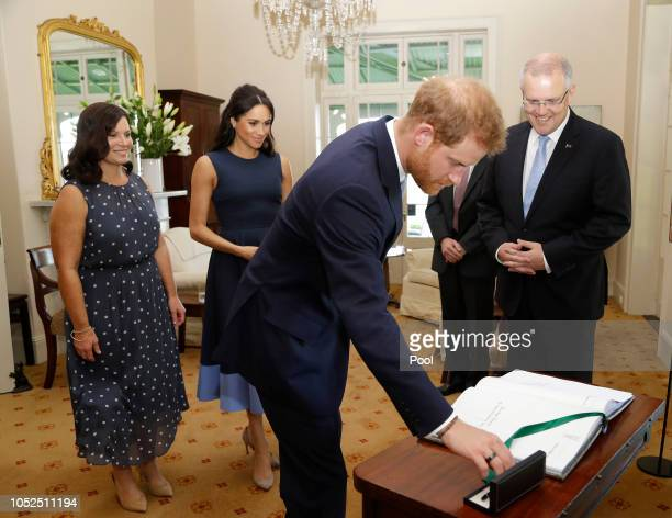 Prince Harry Duke of Sussex signs a visitors book as he and Meghan Duchess of Sussex meet Prime Minister of Australia Scott Morrison and his wife...