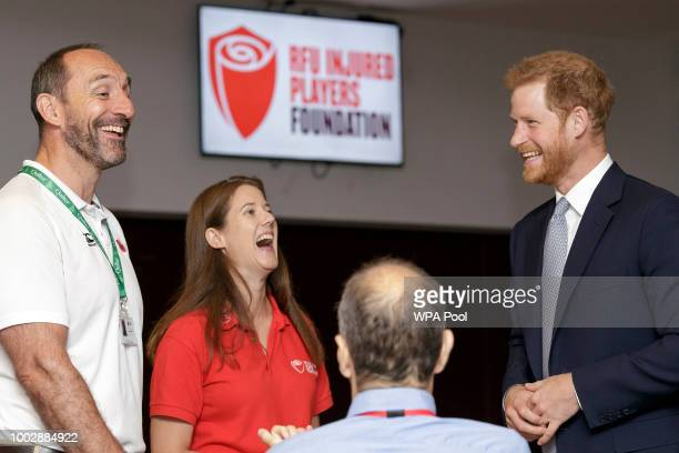 Prince Harry Duke of Sussex smiles as he talks with Karen Hood head of the Injured Players Foundation and Dean Holder IPF welfare officer during a...