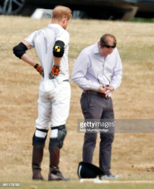 Prince Harry Duke of Sussex stretches his back whilst he has his sunglasses cleaned for him by his polo manager Andrew Tucker during the Audi Polo...