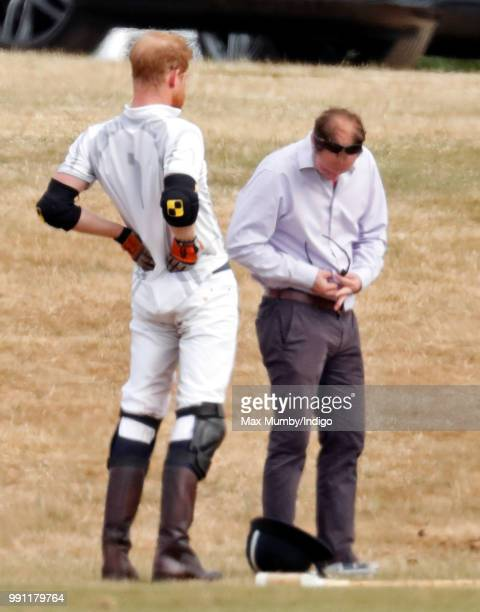 Prince Harry, Duke of Sussex stretches his back whilst he has his sunglasses cleaned for him by his polo manager Andrew Tucker during the Audi Polo...