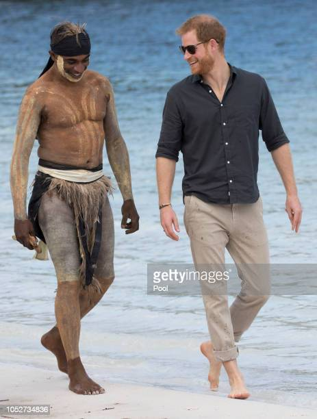 Prince Harry Duke of Sussex talks to aboriginal 'Song Man' Aaron Henderson on the shore of Lake McKenzie where he took part in an aboriginal...