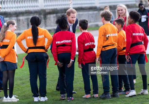 Prince Harry, Duke of Sussex, the Patron of the Rugby Football League talks to children from a local school after watching them play rugby league in...