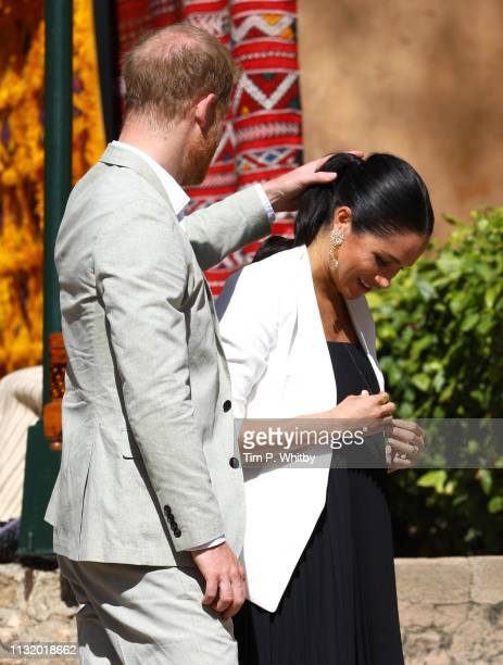 Prince Harry Duke of Sussex touches the hair of Meghan Duchess of Sussex as she tries on an item from a merchant in the walled public Andalusian...
