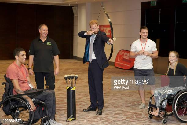 Prince Harry Duke of Sussex tries archery as he meets Liam OKeefe from Bristol with Dani Watts from London during a visit to the RFU Injured Players...