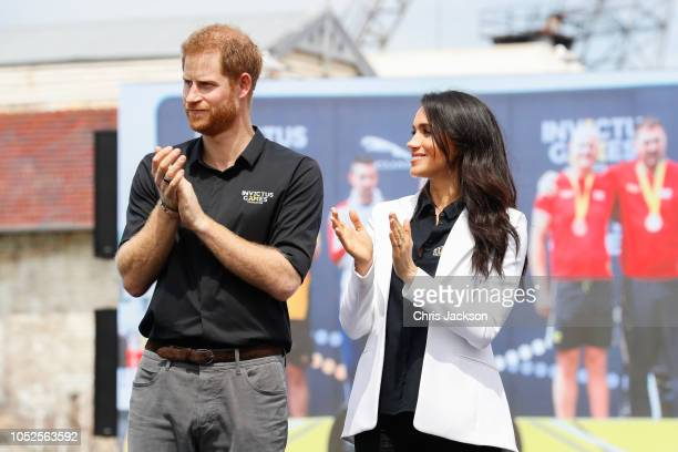 Prince Harry Duke of SussexÊandÊMeghan Duchess of Sussex aplauding the competitors during the JLR Drive Day at Cockatoo Island on October 20 2018 in...