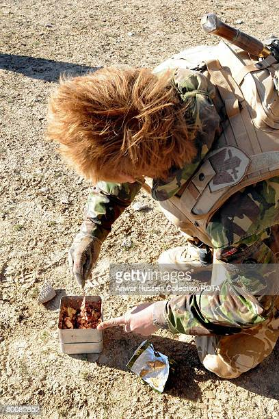 Prince Harry eats a breakfast of biscuits mixed with jam and butter in the desert on February 19 2008 in Helmand Province Afghanistan