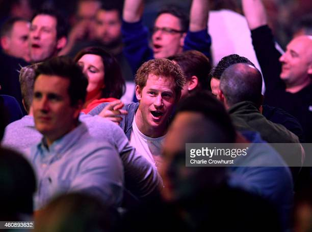 Prince Harry enjoys the darts match between Stephen Bunting of England and James Wade of England with friends during the William Hill PDC World Darts...
