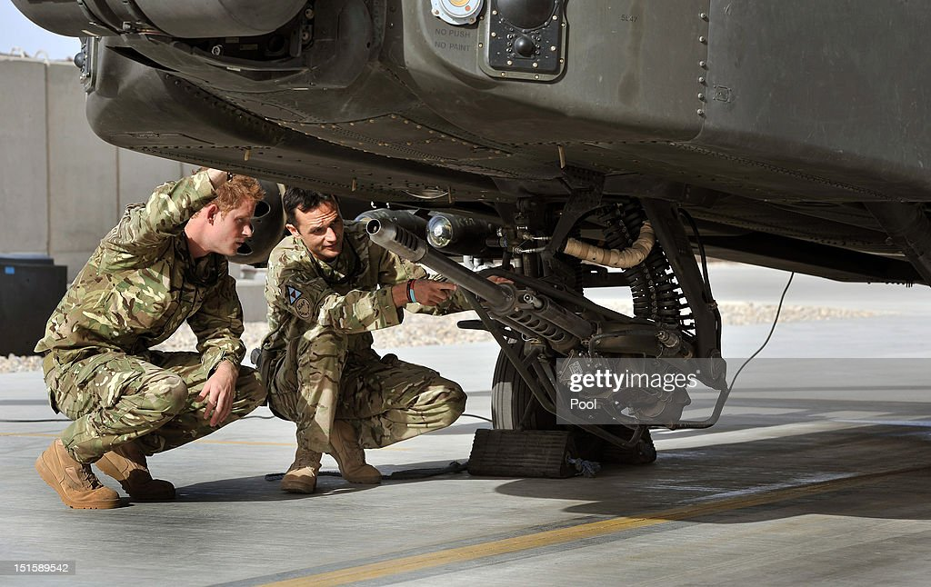 Prince Harry examines the 30mm cannon of an Apache helicopter with a member of his squadron (name not provided) on September 7, 2012 at Camp Bastion, Afghanistan. Prince Harry has been redeployed to the region to pilot attack helicopters.