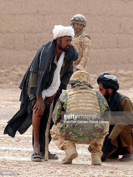 Prince Harry examines the leg of a local Afghan man and tells him the route around a British Army cordon with the help of an Afghan interpreter in...