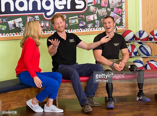 Prince Harry gestures after being asked by one of the audience of children if he will ever become King as he sits flanked by presenter Di Dougherty...