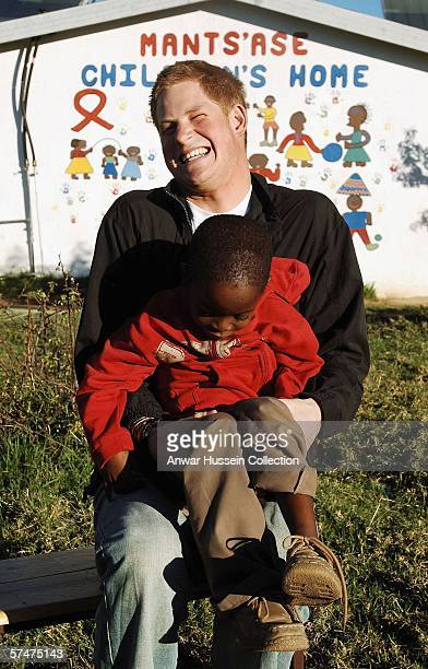 Prince Harry giggles as he holds old friend Mutsu Potsane in the grounds of the Mants'ase childrens home while on a return visit to Lesotho on April...