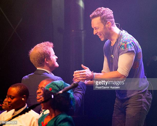 Prince Harry greets Chris Martin as he appears on stage with Coldplay during the Sentebale Concert at Kensington Palace on June 28 2016 in London...