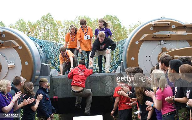 Prince Harry helps Bear Grylls climb a wall at the launch of The Soldier Challenge 2011 at The Imperial War Museum on November 5 2010 in London...