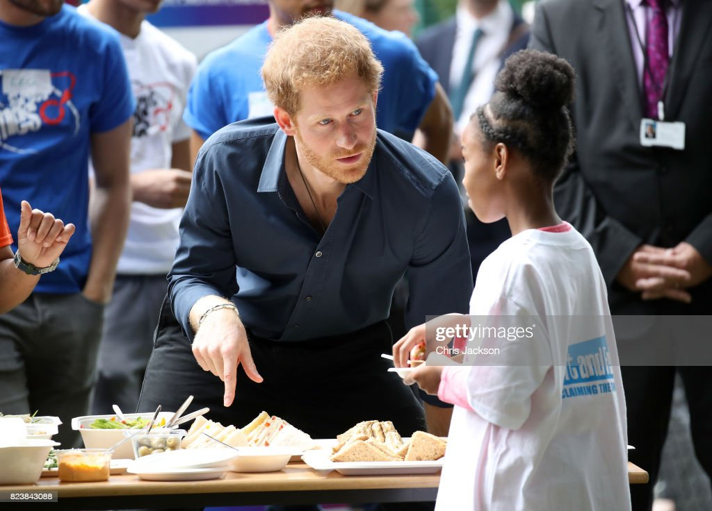 Prince Harry helps to serve lunch during a visit to StreetGames' Fit and Fed at Central Park East Ham on July 28, 2017 in London, England. The Fit and Fed campaign aims to provide children and young people with access to activity sessions during the summer.