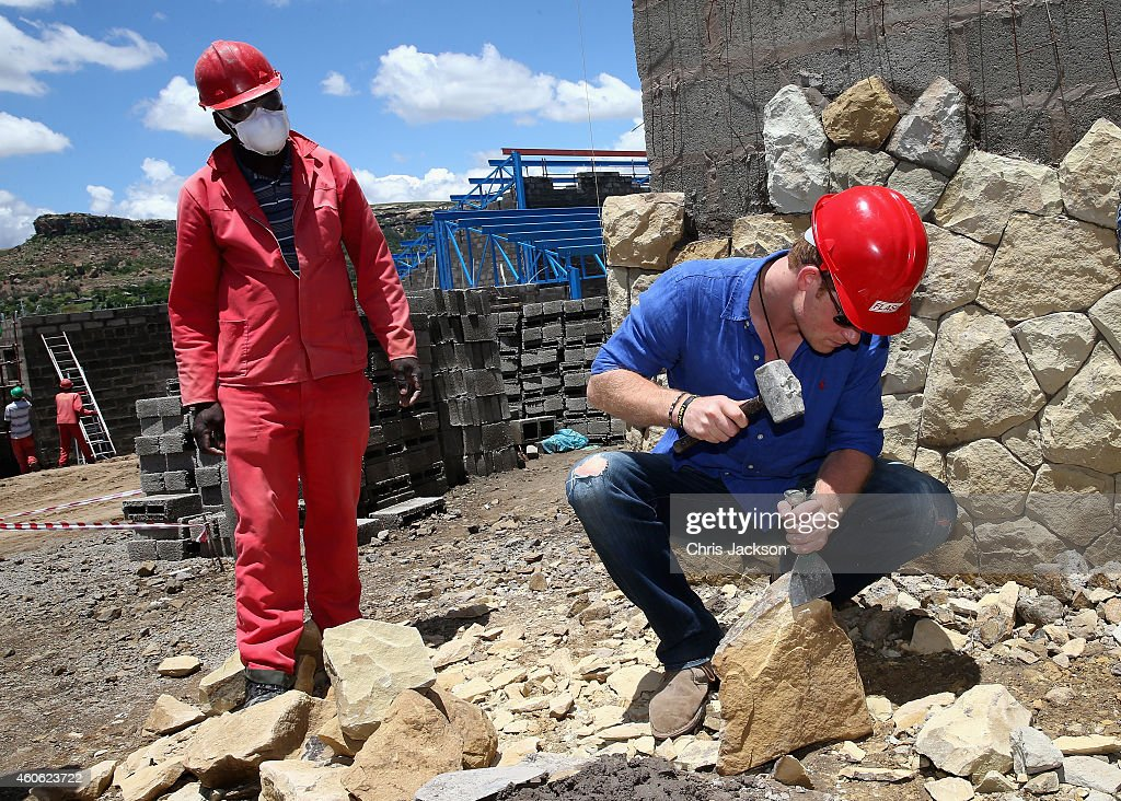 Prince Harry helps with sandstone cladding for the guardhouse as he visits the construction site for the new Sentebale Mamohato Children's Centre at Thaba-Bosiu on December 10, 2014 in Maseru, Lesotho. Prince Harry was visiting Lesotho to see the work of his charity Sentebale. Sentebale provides healthcare and education to vulnerable children in Lesotho, Southern Africa. Prince Harry said 'The last time I was on the site was before we'd 'broken ground,' so to see the progress so far was absolutely amazing. 135 workers on site, all the buildings are half done, and a dining hall that Hogwarts would be proud of. This is a serious project, far bigger in bricks than it is on paper. This is the perfect setting - the sacred land at Thaba-Bosiu given to us by His Majesty King Letsie. We can't wait for it to be finished and full of smiling, screaming children and hopefully this wall will still be standing.'