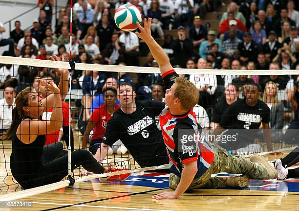 Prince Harry hits the ball to former U.S. Olympic beach volleyball great Misty May-Treanor as they play sitting volleyball with the UK team at a...