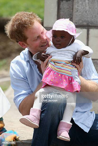 Prince Harry holds a baby during a visit to a herd boy night school constructed by Sentebale on December 8 2014 in Mokhotlong Lesotho Prince Harry...