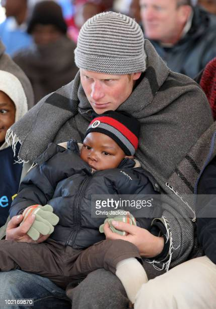 Prince Harry holds a young boy during a visit to a child education centre on June 17 2010 in Semonkong Lesotho The two Princes are on a joint trip to...