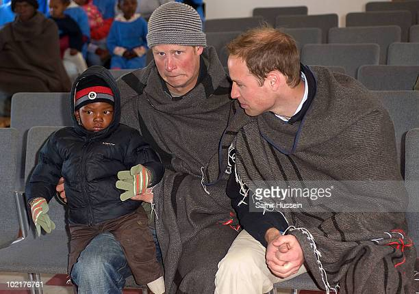 Prince Harry holds a young boy on his knee as he and Prince William visit the Semongkong Children's Centre on June 17 2010 in Semongkong Lesotho The...