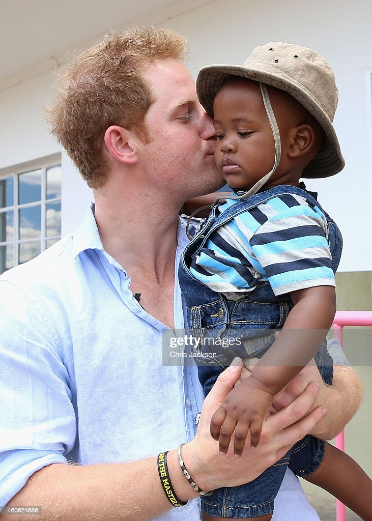 Prince Harry holds a young child during a visit to Thuso Centre for children living with multiple disabilities on December 7, 2014 in Bute-Bute, Lesotho. Prince Harry was visiting Lesotho to see the work of his charity Sentebale. Sentebale provides healthcare and education to vulnerable children in Lesotho, Southern Africa. The particular theme of his visit was to check on the progress of the Mamohato Childrens Centre which will provide vital support to children affected by HIV. Prince Harry founded Sentebale (which means Forget Me Not in Sesotho) with Prince Seeiso in 2006.