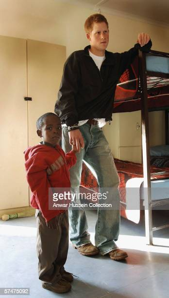Prince Harry holds hands with his old friend, Mutsu Potsane, as he inspect the sleeping rooms of the Mants'ase children's home while on a return...