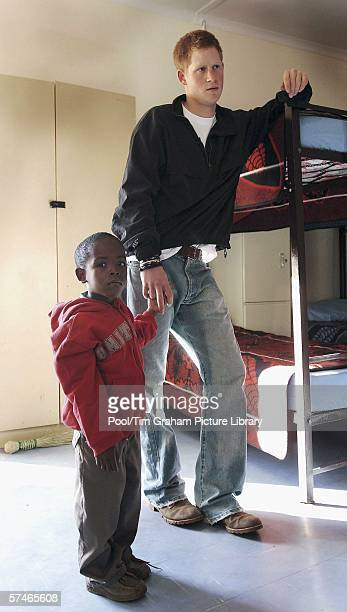 Prince Harry holds hands with old friend, Mutsu Potsane, as he inspect the sleeping rooms of the Mants'ase children's home, while on a return visit...