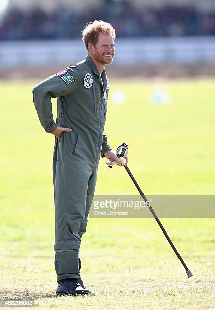 Prince Harry holds on to year old RAF veteranTom Neil's walking stick as he watches the Spitfires take off on the airfield at Goodwood Aerodrome...