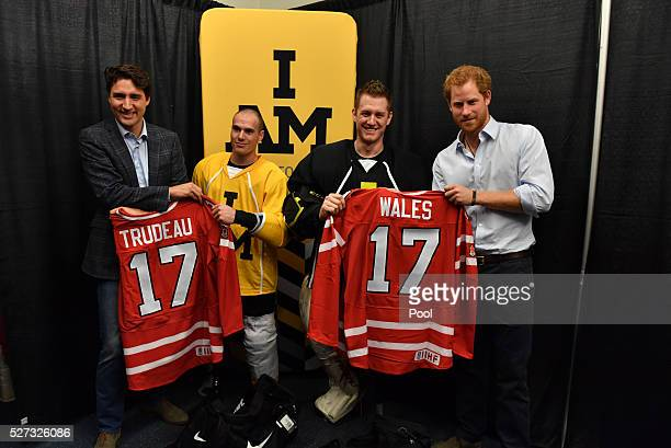 Prince Harry holds the Wales hockey jersey up with Canadian Prime Minister Justin Trudeau as they meet with Invictus Games athletes after a...