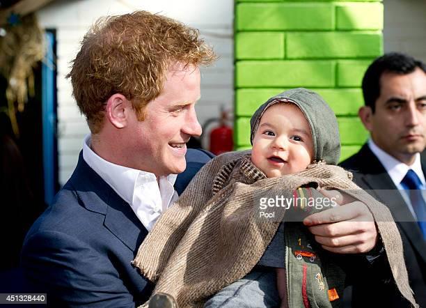 Prince Harry holds young Matias Gonzalez as he visits a the Sagrada Familia kindergarten a kindergarden of indigenous children on June 27 2014 in...