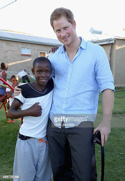 Prince Harry hugs a young boy called Mutso during a visit to the Mants'ase Children's Home on December 5 2014 in Mohales Hoek