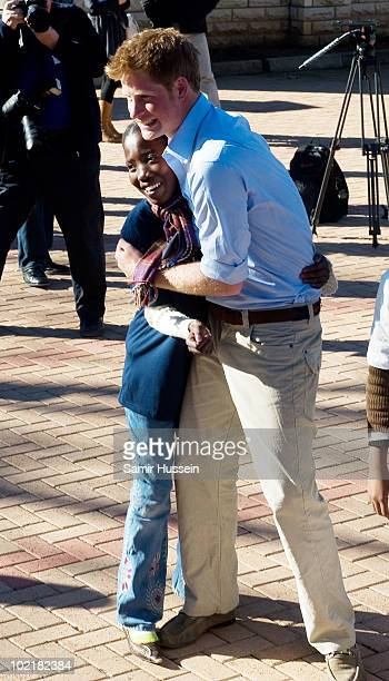 Prince Harry hugs a young girl at the Mamohato Network Club for children affected by HIV at King Letsie's Palace on June 17 2010 in Maseru Lesotho...