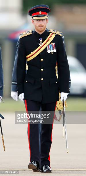 Prince Harry inspects a parade as he on behalf of his grandmother Queen Elizabeth II presents the RAF Regiment with a new Colour in their 75th...
