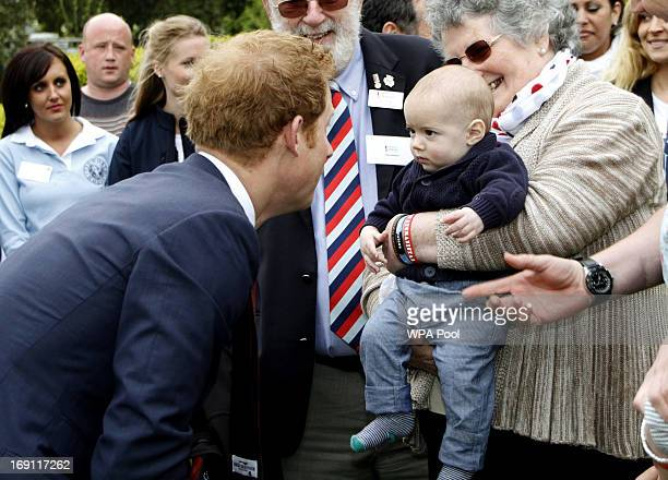 Prince Harry interacts with a young child during his visit to Tedworth House to officially open the charity's Tedworth House recovery centre on May...