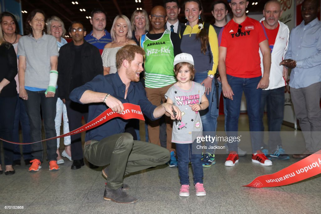 Prince Harry is helped by a young girl to officially open the Virgin Money London Marathon Expo at ExCel on April 19, 2017 in London, England. Prince Harry, who is Patron of the London Marathon Charitable Trust, will meet runners and hand out race numbers, along with special edition 'Heads Together' headbands, which is the official Charity of the Year for this year's marathon.