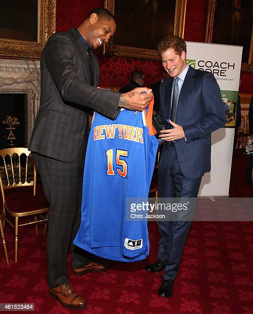 Prince Harry is presented with a basketball shirt and size 15 basketball shoe by NBA AllStar Carmelo Anthony during a CoachCore Graduation event at...