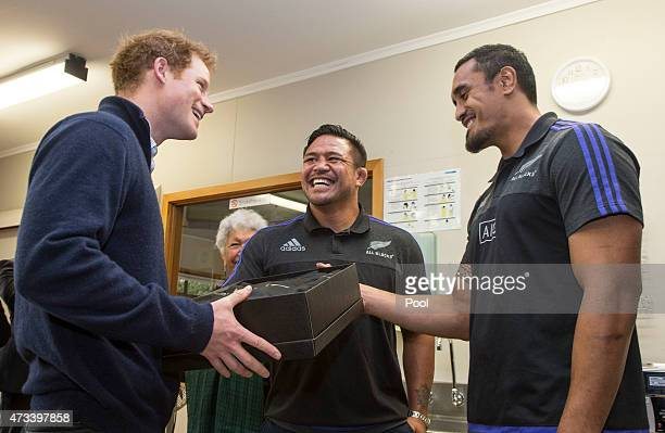 Prince Harry is presented with an All Black Jersey by All Blacks Jerome Kaino and Keven Mealamu as he visits a spinal rehabiltation unit on May 15...