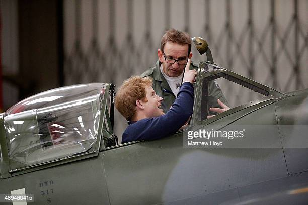 Prince Harry is shown around a Spitfire aircraft at the Boultbee Flight Academy on February 15, 2014 in Goodwood, United Kingdom. Prince Harry met...