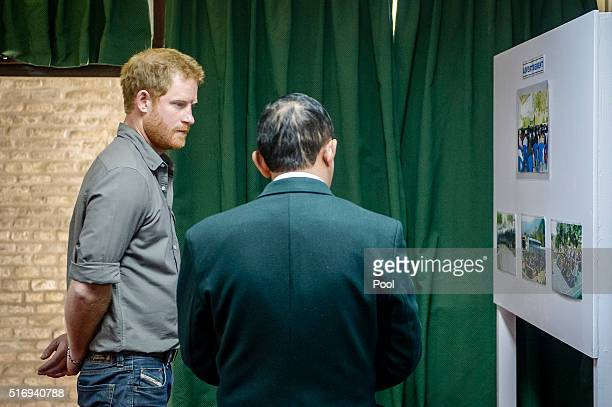 Prince Harry is shown photos of the Gurkha training process at the British Gurkha Camp on March 22, 2016 in Pokhara, Nepal. Prince Harry is on a five...