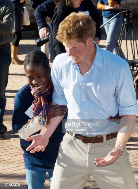 Prince Harry jokes with a young girl at the Mamohato Network Club for children affected by HIV at King Letsie's Palace on June 17, 2010 in Maseru,...