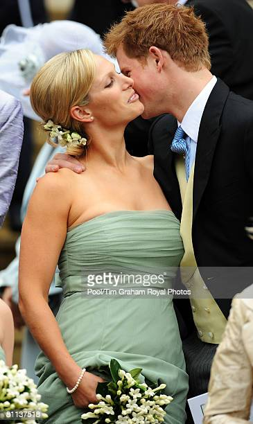 Prince Harry kisses his cousin Zara Phillips who was a bridesmaid at the wedding of Peter Phillips to Autumn Kelly at St George's Chapel in Windsor...