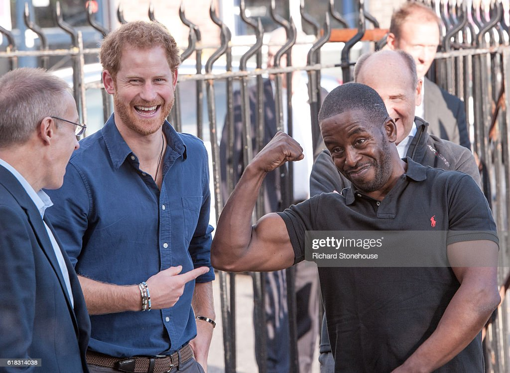 Prince Harry laughs as Centre Manager Trevor Rose shows his muscles as he arrives to visit the Community Recording Studio at Russell Youth Centre on October 26, 2016 in Nottingham, United Kingdom. The Royal Foundation is working with Epic Partners and the Community Recording Studio (CRS) to deliver Full Effect: a project to improve the opportunities for young people and reduce youth violence in St. Ann's, Nottingham.