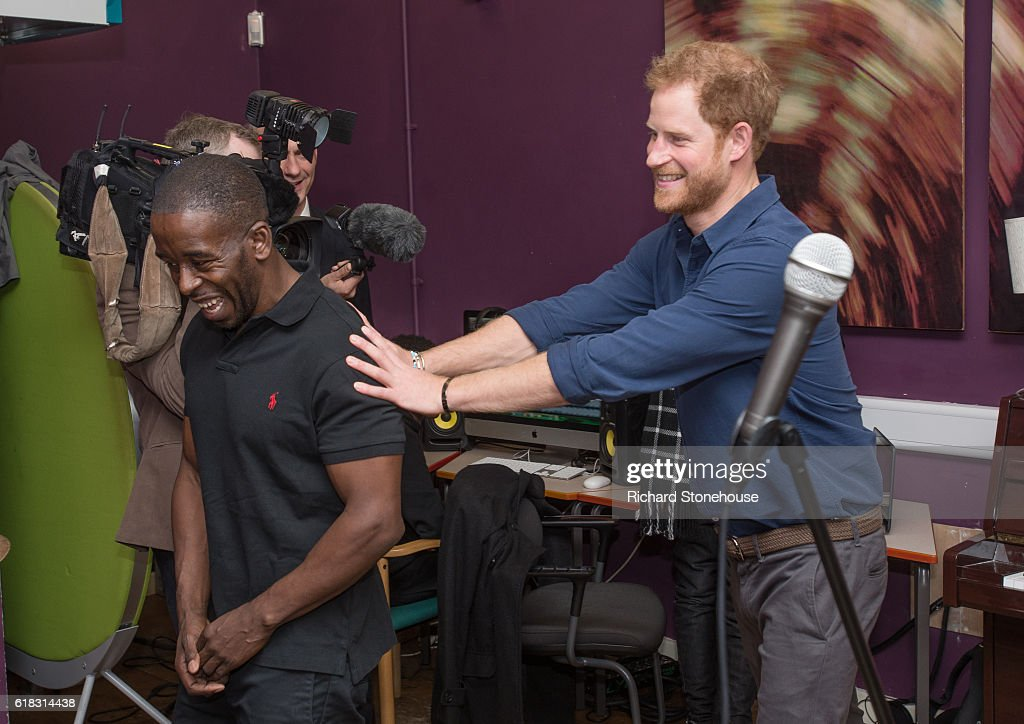 Prince Harry laughs as he pushes Centre Manager Trevor Rose through one of the studios during his visit the Community Recording Studio at Russell Youth Centre on October 26, 2016 in Nottingham, United Kingdom. The Royal Foundation is working with Epic Partners and the Community Recording Studio (CRS) to deliver Full Effect: a project to improve the opportunities for young people and reduce youth violence in St. Ann's, Nottingham.