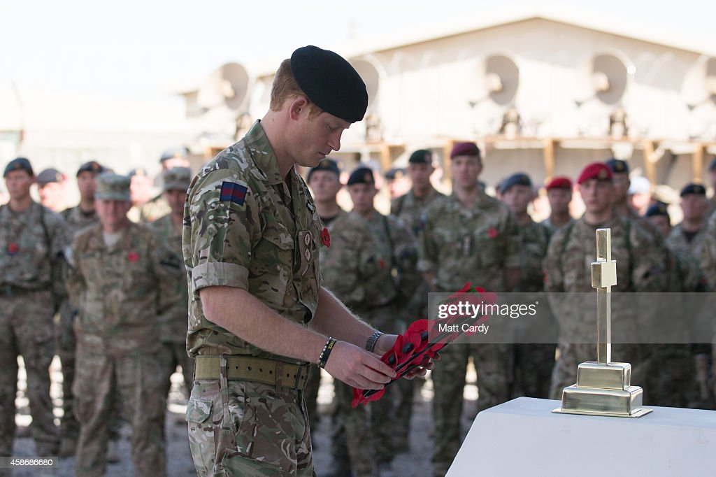 Prince Harry lays a poppy wreath as he joins British troops and service personal remaining in Afghanistan and International Security Assistance Force (ISAF) personnel and civilians as they gather for a Remembrance Sunday service at Kandahar Airfield November 9, 2014 in Kandahar, Afghanistan. As the UK combat mission in Afghanistan draws to an end in 2014 this year, which also marks the 100th anniversary of the start of World War One, 70 years since the D-Day landings will be the last time British service personal will gather in any great numbers in the south of the country.