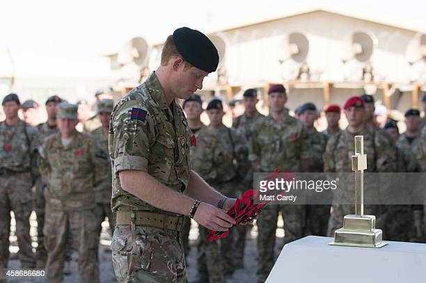 Prince Harry lays a poppy wreath as he joins British troops and service personal remaining in Afghanistan and International Security Assistance Force...