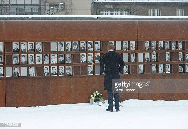 Prince Harry lays a wreath in the snow as he visits the Bernauer Strasse Wall Memorial on December 19 2010 in Berlin Germany The Wall memorial...
