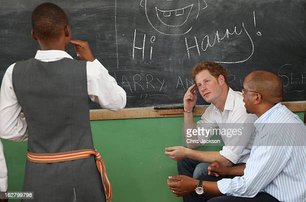 Prince Harry learns sign language as he visits the Kananelo Centre for the deaf, a project supported by his charity Sentebale on February 27, 2013 in...