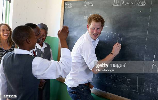 Prince Harry learns sign language from deaf children during at visit to the Kananelo Centre for the deaf a project supported by his charity Sentebale...